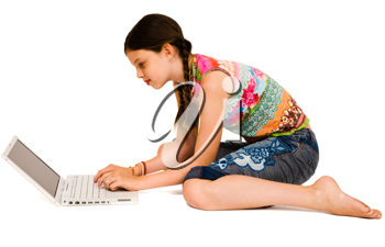 Royalty Free Photo of a Young girl Sitting on the Floor Using a Laptop