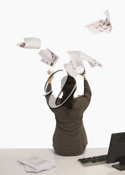 Businesswoman tossing documents in an office