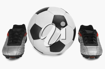 Close-up of a soccer ball with a pair of shoes