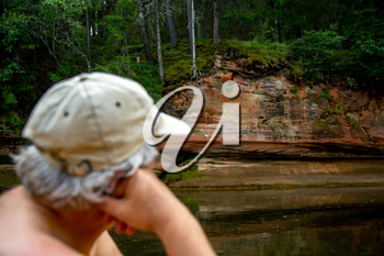 Man at the rock. Portrait of man at the rock,  on coast of the river. The man looks at the cliff. Rock on the Gauja river. Cliff is steep rock face, especially at the edge of the river or the sea. Man is out of focus.