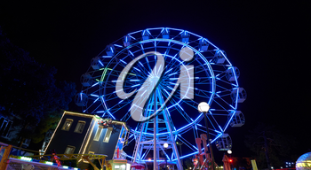 Amusement park at night with a ferris wheel and carousels.