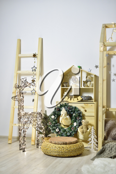 Children's playroom with wooden furniture, a house decorated for the New Year holiday with a Christmas tree, and a luminous deer from garlands.