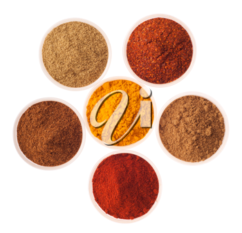 collection of indian spices (cumin, coriander, paprika, garam masala, curcuma, red pepper flakes) on glass cups isolated on white background