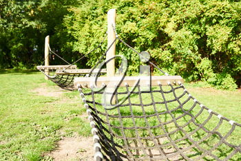 Large rope hammock hanging on poles in a backyard