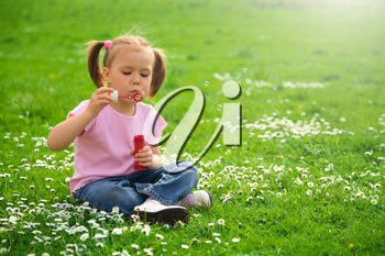 Royalty Free Photo of a Little Girl Sitting on the Grass Blowing Bubbles