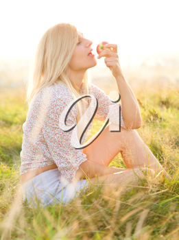 Royalty Free Photo of a Woman Eating an Apple Outside