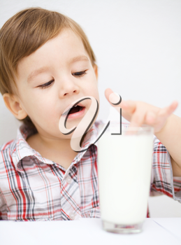 Cute little boy is dipping his fingers in the glass of milk