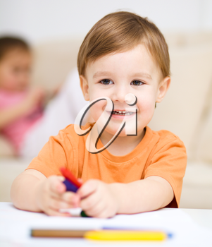 Little boy is drawing on white paper using crayon, his sister sits behind him
