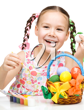 Little girl preparing eggs for Easter, isolated over white