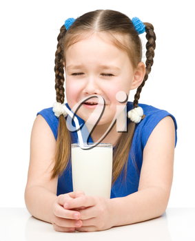 Sad little girl with a glass of milk, isolated over white