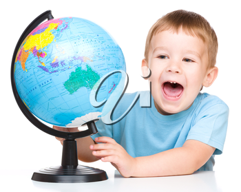 Happy little boy with a globe, isolated over white