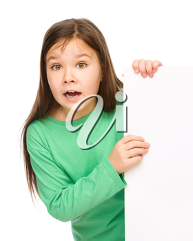 Little girl is looking out from the blank banner, opening her mouth in astonishment, isolated over white