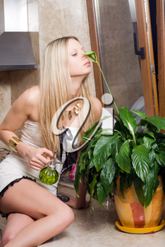 Royalty Free Photo of a Woman Smelling a Plant