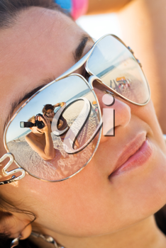 Royalty Free Photo of a Photographer and Woman Reflected in a Woman's Sunglasses