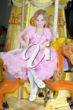 Beautiful little girl in pink dress sitting on a carousel pony