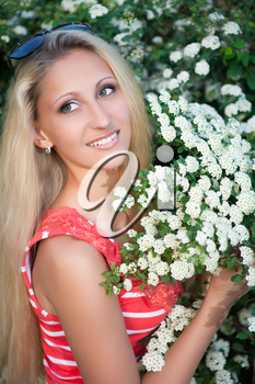 Young blond woman posing near the flowering bush
