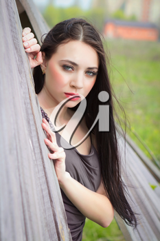 Portrait of pretty brunette posing behind the wooden fence