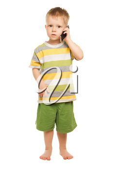 Little boy in shorts and t-shirt posing with the mobile phone. Isolated on white