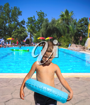 Serious kid stands near the pool in the spa resort
