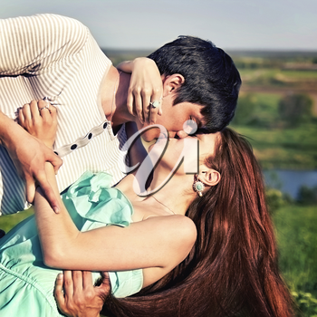 summer outdoor portrait of a young couple kissing