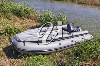Outboard rubber boat pulled to the riverbank