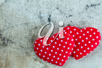 Two decorative hearts on dirty canvas background