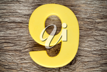 Yellow number nine on the wooden background
