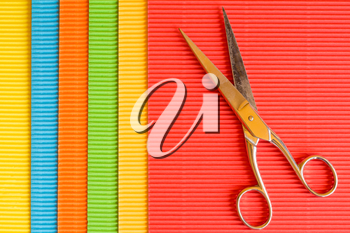 Old scissors on colored corrugated paper background