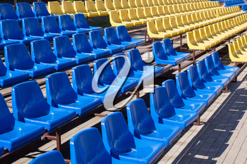Row of blue and yellow chairs in stadium