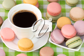 Delicious french macaroons with cup of black coffee