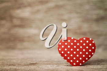 Red polka dot heart on wooden background