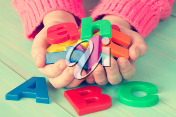 Child learning to read using magnetic letters. Education School Knowledge Concept
