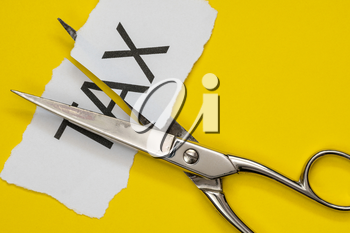 Scissors and printed paper with the word tax on it cut in half. Tax cuts concept