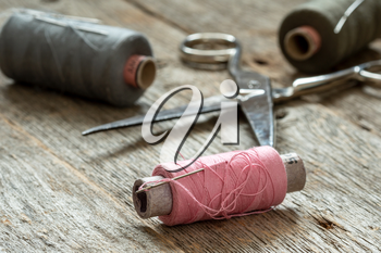 Spools of thread and scissors on wooden background