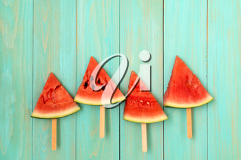 Watermelon slice popsicles on a blue wood background