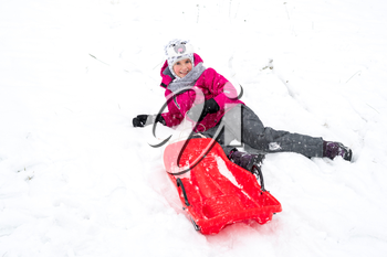 Happy girl enjoying a sleigh ride, play outdoors in snow.