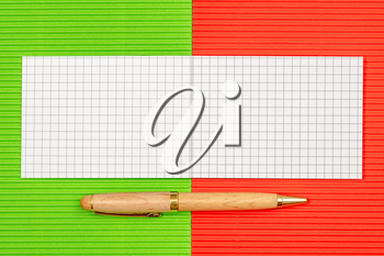 Small notebook with a pen on the colorful paper background. Copy-space.