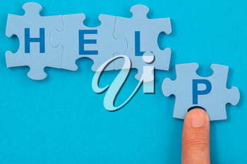 Concept of help, finding solution. Finger and puzzle with word HELP on the blue background