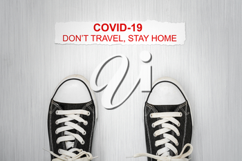 Shoes and note with phrase Don't travel, stay home.Stop coronavirus. Self isolation. Home quarantine from Covid-19. Recommendation to prevent spreading Coronavirus, Covid 19 lockdown.