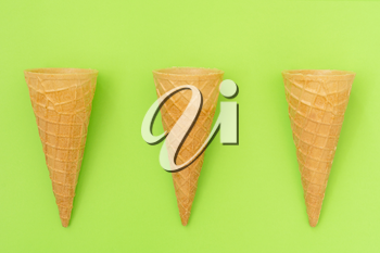 Three sweet wafer cones on green background