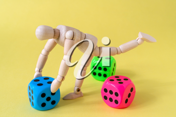 Wooden man figure with game dice on yellow background.