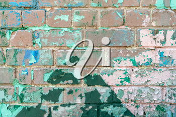 Weathered brick wall with peeling green paint. Close up view.