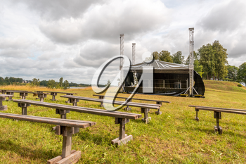 Empty rows of  wooden benches with the stage in the open air