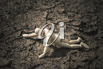 Wooden man lying on cracked earth in the arid area. Thirst and dehydration.
