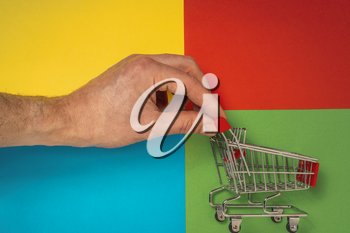 A hand pushing a red shopping cart on a colored background