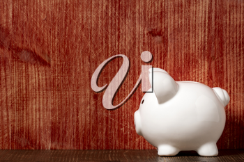 White ceramic piggy bank on the old wooden shelf. Copy space.