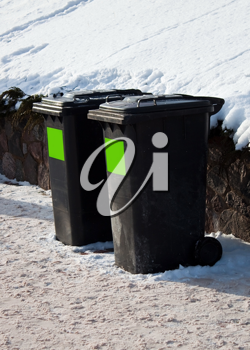 Two plastic trash containers in the winter steet