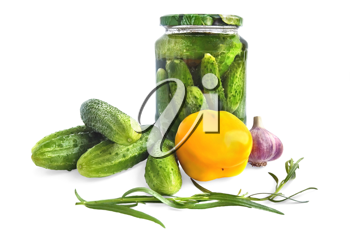 Cucumbers in a glass jar and on the table, yellow bell pepper, garlic, tarragon isolated on a white background