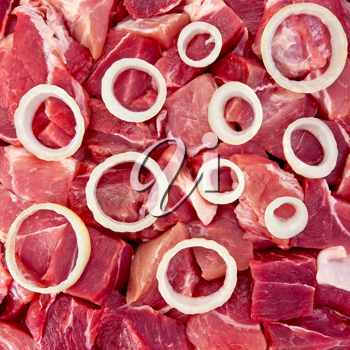 The rings of white onion on a background of red pieces of meat (texture)