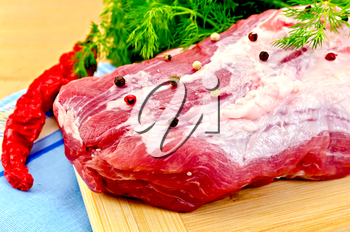 Large piece of meat with peas of different peppers, red pepper, parsley and dill, blue cloth on the background of wooden boards